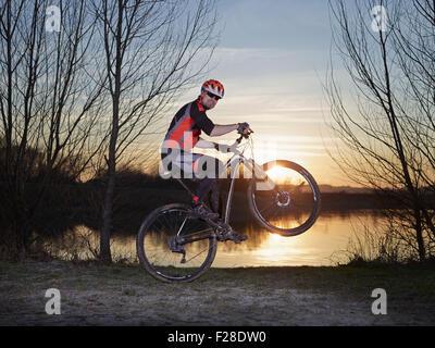 Reifer Mann tun Stunts auf Mountainbike bei Sonnenuntergang, Bayern, Deutschland - Stockfoto