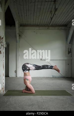 Mitte Erwachsene Frau üben Kopfstand Pose im Yoga-Studio, München, Bayern, Deutschland - Stockfoto
