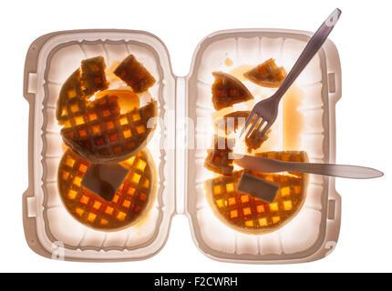 Blick geradeaus hinunter auf Waffeln mit Butter und Sirup in einem Plastikbehälter mit Messer und Gabel, halb gegessen - Stockfoto