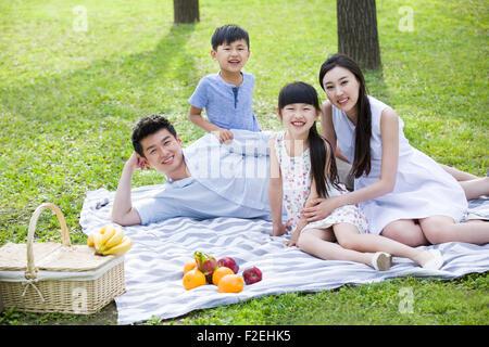 Glückliche junge Familie Picknick auf dem Rasen - Stockfoto