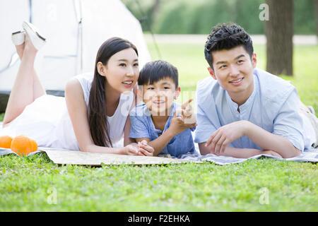 Glückliche junge Familie liegen auf dem Rasen - Stockfoto