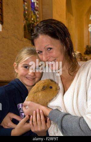 Mutter und 10 jährige Tochter und ihre Meerschweinchen an der Kirche, in die Gemeinde eingeladen wurden, ihre Haustiere - Stockfoto