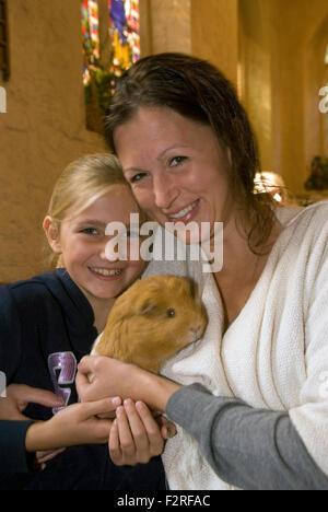 Mutter und 10 jährige Tochter und ihre Meerschweinchen an der Kirche, in die Gemeinde eingeladen wurden, mitbringen... - Stockfoto