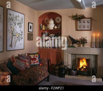Jahrhundert · Kamin Mit Beleuchteten Feuer Im Wohnzimmer Mit Alkoven Regal   Und Gemusterten Sofa Gestapelt Mit Ethnischen