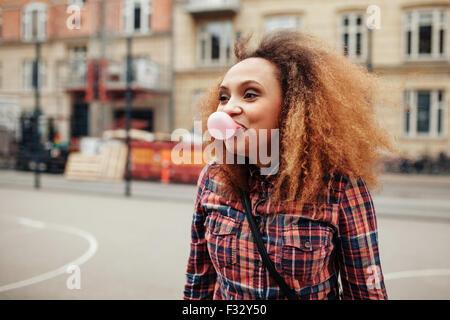 Junge Afrikanerin eine Seifenblase mit ihrem Kaugummi. Lässige junge Frau auf Stadtstraße Spaß. - Stockfoto
