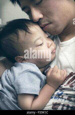 Jungen schlafen in des Vaters Schoß - Stockfoto