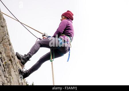 Weiblichen Rock Climber mit Sicherungsseil und Klettergurt auf eine Felswand Abseilen. North Wales, UK, Großbritannien - Stockfoto