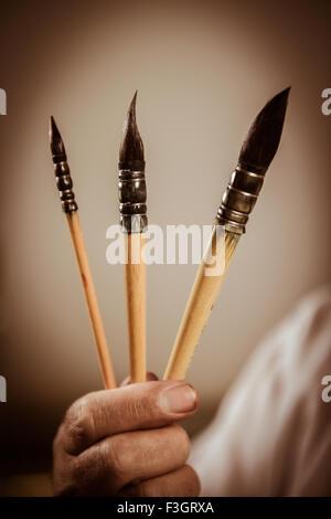 Des Malers Hand hält drei Pinsel - Stockfoto