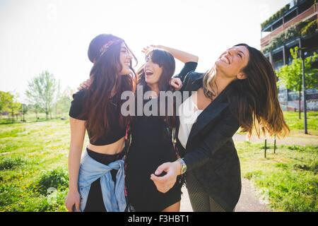 Drei jungen Freundinnen lachen zusammen im park - Stockfoto
