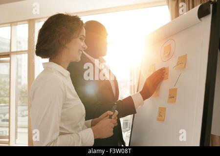 Zwei Kollegen zusammen am Projekt arbeiten. Geschäftsleute, die ihre Ideen auf Whiteboard während einer Präsentation - Stockfoto