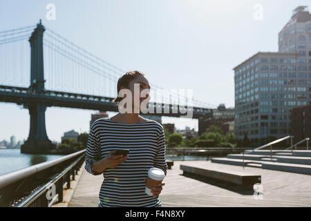 USA, New York City, Porträt der jungen Frau mit Smartphone und Kaffee zu gehen - Stockfoto