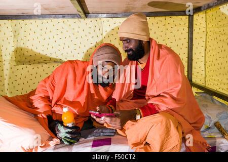 Zwei Sadhus, die heiligen Männer, spielen mit einem Smartphone in einem Zelt - Stockfoto
