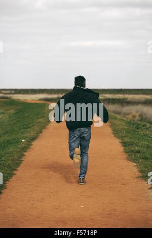 Mann mittleren Alters im ländlichen Küstenregion laufen - Stockfoto