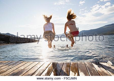 Junge Frauen aus dem Dock in See springen - Stockfoto