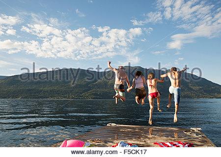 Junge Freunde aus dem Dock in See springen - Stockfoto