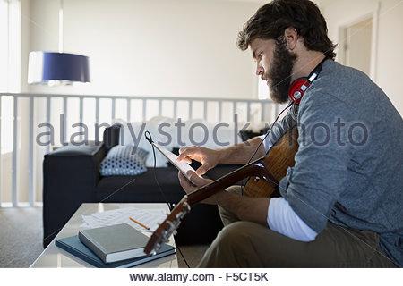 Mann mit Gitarre Musikaufnahmen mit digital-Tablette - Stockfoto
