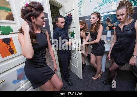Mann in der Toilette mit betrunkenen Frauen - Stockfoto