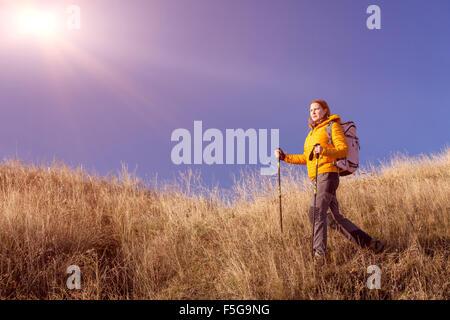 Weibliche Wanderer zu Fuß auf grasbewachsenen Hügel - Stockfoto