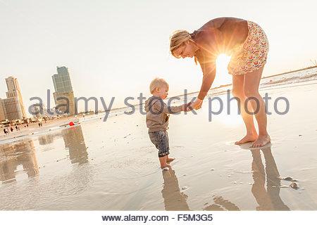 Vereinigte Arabische Emirate, Dubai, Frau mit Sohn (12-17 Monate) am Strand bei Sonnenuntergang - Stockfoto