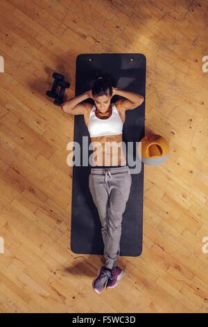 Passen Sie junge Frau liegt auf Gymnastikmatte Magen Übungen. Draufsicht der weiblichen trainieren Sie im Fitness - Stockfoto