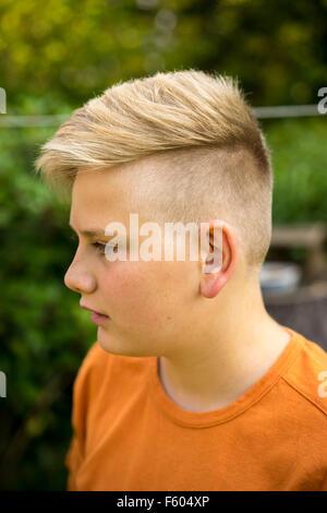Hübscher Junge Teenager mit einem trendigen blonde Frisur stehen draußen im Garten, schließen Sie Kopf und Schultern - Stockfoto