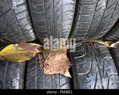 Nahaufnahme eines strukturierten Gummireifen mit Blättern - Stockfoto