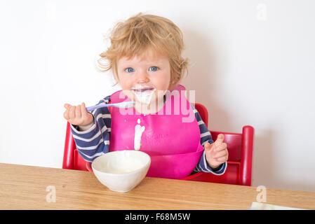1 Jahr altes Baby Essen Joghurt messily, England, UK - Stockfoto