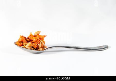 Einen Löffel der Butternut-Kürbis Samen vor einem weißen Hintergrund - Stockfoto