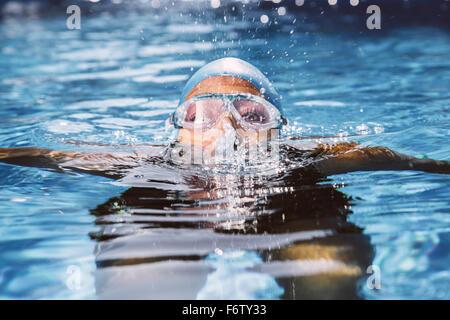 Weibliche Triathlonien mit Brille sprudeln aus Wasser im Schwimmbad - Stockfoto