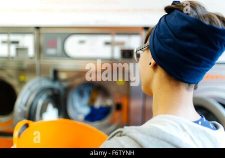 Rückansicht der junge Frau in einen Waschsalon - Stockfoto