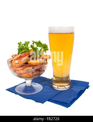 Bier im Glas und Teller mit Garnelen auf weißem Hintergrund - Stockfoto