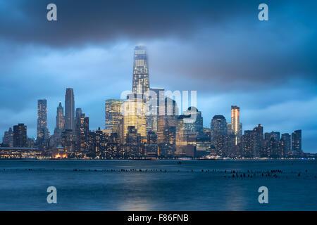 Lower Manhattan und Financial District beleuchtet Wolkenkratzer mit Gewitterwolken, New York City. World Trade Center - Stockfoto
