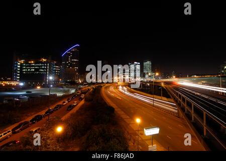Londons Canary Wharf Financial District-Gebäude in der Nacht mit Autobahnverkehr und Docklands Light Railway (DLR) - Stockfoto