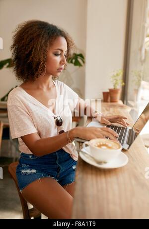 Innenaufnahme der junge lässige Frau sitzt in einem Café mit Laptop. Afrikanische Mädchen Surfen Internet auf ihrem - Stockfoto