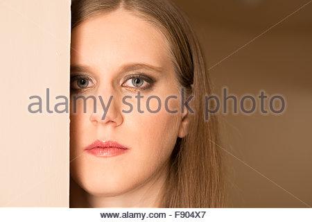 Schuss in den Kopf einer jungen Frau mit ihrem Gesicht teilweise durch eine Wand blockiert. - Stockfoto
