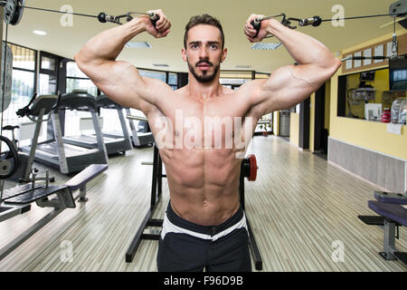 Junger Mann Bodybuilder arbeitet an seinen Bizeps mit Kabeln In einem Fitnessstudio - Stockfoto