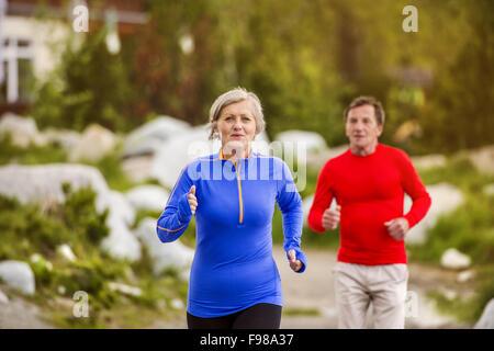 Älteres paar jogging Runde Tarn in wunderschöne Berge, Hügel und Hotel im Hintergrund - Stockfoto