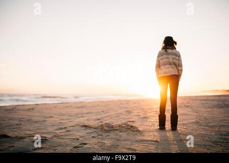 Rückansicht der jungen Frau am Strand im winter - Stockfoto