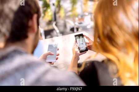 Rückansicht des jungen Paares sitzen nebeneinander mit ihren smartphones - Stockfoto