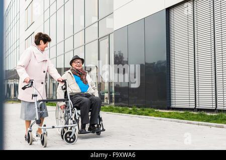 Ältere Frau mit Rädern Walker und senior Mann im Rollstuhl auf Bürgersteig - Stockfoto