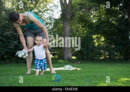 Mutter hilft ihrem Babyjungen, erste Schritte, München, Bayern, Deutschland - Stockfoto