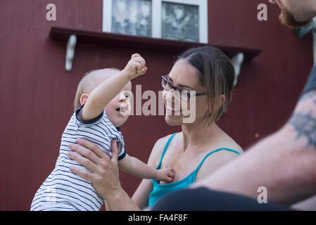 Baby Junge in den Armen seiner Mutter anbietennahrung zu seinem Vater, München, Bayern, Deutschland - Stockfoto