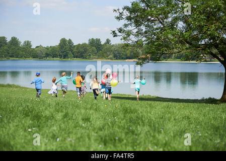 Rückansicht des Kinder laufen im Park mit Luftballons, See Karlsfeld, München, Bayern, Deutschland - Stockfoto