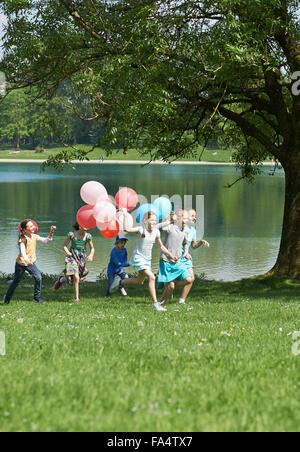Kinder laufen im Park mit Luftballons, München, Bayern, Deutschland - Stockfoto