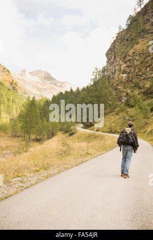 Rückansicht des Reifen Wanderer zu Fuß auf Mountain Road, Österreichische Alpen, Kärnten, Österreich - Stockfoto