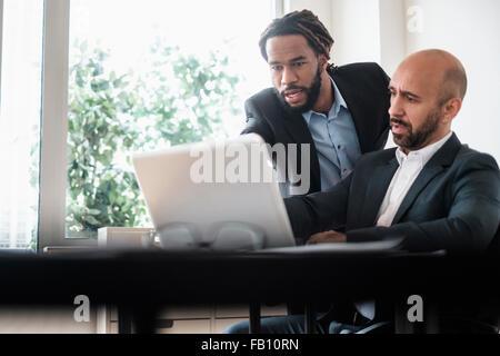 Zwei Geschäftsleute arbeiten mit Laptop Schreibtisch im Büro - Stockfoto