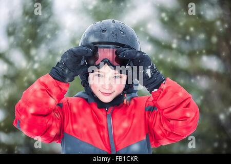 Junge Schutzbrille tragen Helm und Skifahren mit Blick auf die Kamera zu Lächeln, schneit - Stockfoto