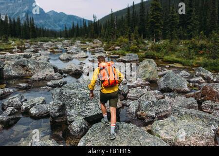 Rückansicht des Mitte erwachsener Mann mit Rucksack zu Fuß auf felsigen Flussbett, Moraine Lake, Banff Nationalpark, - Stockfoto