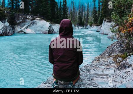 Hintere Ansicht Mitte erwachsenen Mann mit Kapuze wasserdicht beschichten hockend Gewässer Rand Moraine Lake-Banff - Stockfoto
