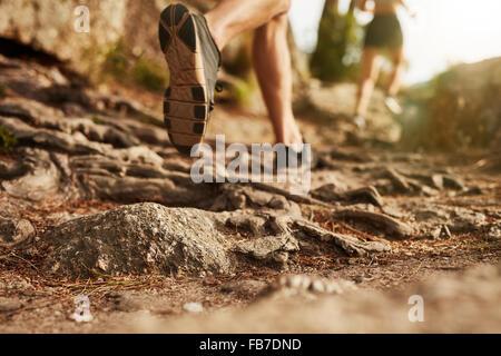 Querfeldein laufen. Nahaufnahme der männliche Füße laufen durch felsiges Gelände. Fokus auf Schuhe. - Stockfoto